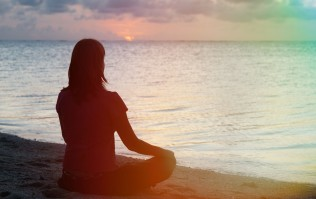 45150428 - young woman meditation on sunset tropical beach